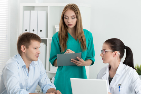 healthcare workers: Female medicine doctor with her colleague consulting male patient. Healthcare and medicine concept.
