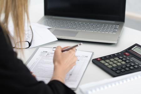 税務フォームを記入女性の手のショットを閉じる。貯蓄、財政および経済の概念 写真素材