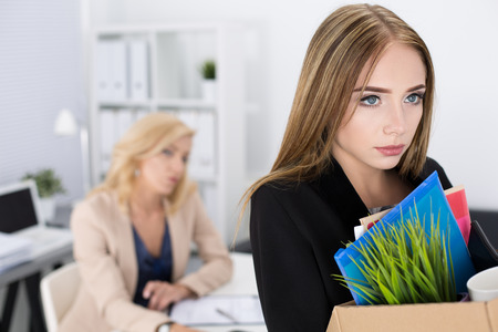 boss: Boss dismissing an employee. Dejected fired office worker carrying a box full of belongings. Getting fired concept.