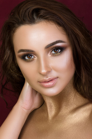 a close up: Beauty portrait of young pretty woman with fashion make-up. Bronzed skin and golden smokey eyes.