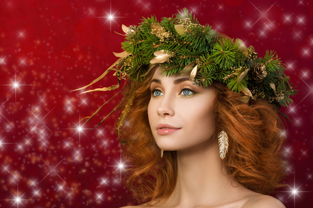model portrait: Portrait of young beautiful redhaired woman with firry wreath with golden leaves in her hair. Christmas and new year concept