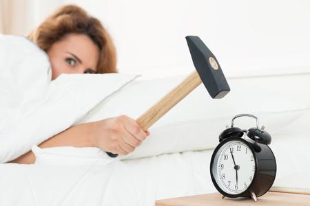 despertarse: Mujer joven que intenta romper la alarma con el martillo. Temprano en la mañana al despertar.