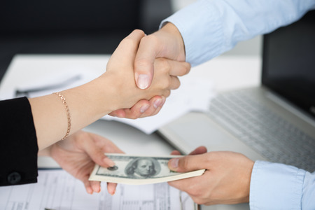 venality: Woman and man handshake close up with the money in the other hands. Deal, venality, bribe, corruption concept