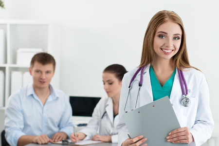 consulting team: Portrait of smiling female medicine doctor with her colleague consulting male patient at background. Healthcare and medicine concept.