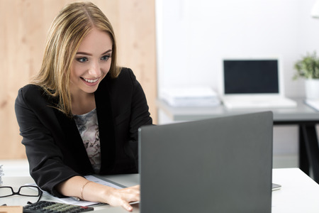 chatting: Young smiling business woman working at laptop in the office. Businesswoman chatting with someone online. Stock Photo