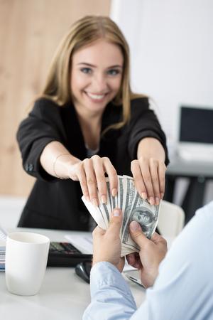 remuneraciones: Mujer que toma lote de billetes de cien dólares. Venalidad, cohecho, concepto corrupción
