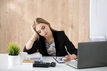 Moe zakenvrouw zit op haar werkplek. Overwerk, overuren en stress op het werk concept. Stockfoto