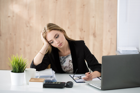 agotado: Mujer de negocios cansado que se sienta en su lugar de trabajo. El exceso de trabajo, las horas extraordinarias y el estrés que trabaja en el concepto de trabajo.