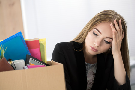 belongings: Young dismissed female worker in office sitting near carton box with her belongings. Getting fired concept. Stock Photo