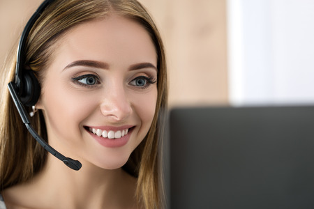 Portret van mooie call center operator op het werk. Vrouw met hoofdtelefoon praten met iemand online Stockfoto