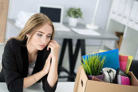 unemployed dismissed: Young dismissed female worker in office sitting near carton box with her belongings. Getting fired concept. Stock Photo