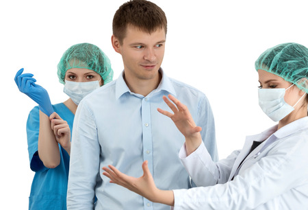 colonoscopy: Female doctor in cap and face mask putting on blue protective glove standing behind the scared patient. Her colleague preparing him to the examination. Prostatitis prophylaxis. Men health. Healthcare, medical, surgery and team work concept Stock Photo