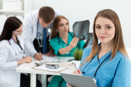 medical services: Portrait of smiling female medicine doctor holding folder with documents with her three colleagues working at background. Healthcare and medicine concept.