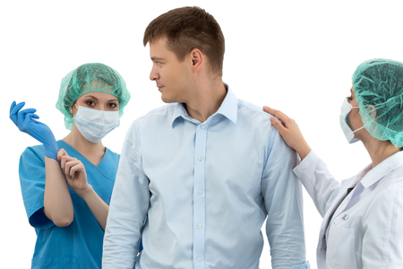 to reassure: Female doctor in cap and face mask putting on blue protective glove standing behind the scared patient. Her colleague is trying to reassure him. Medical examination. Prostatitis prophylaxis. Men health. Healthcare, medical, surgery and team work concept