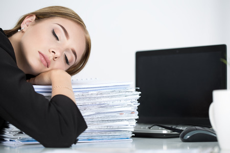 sleeping at desk: Tired business woman slleeping on heap of papers at her working place. Overwork, working overtime and stress at work concept.