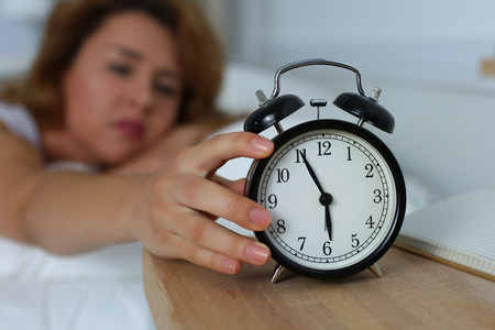oversleep: Young sleepy woman trying to turn off the alarm clock. Early morning waking up. Stock Photo