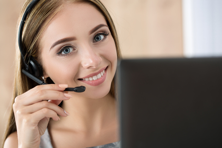 Portrait of beautiful call center operator at work. Woman with headset talking to someone online Foto de archivo