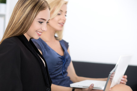 office workers: Two beautiful business women sitting at seminar and writing something. Business education and success concept