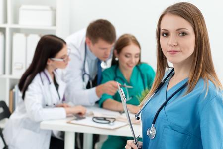 medicamento: Retrato de la sonrisa carpeta celebración de la medicina doctora con documentos con sus tres colegas que trabajan en segundo plano. Salud y concepto de la medicina. Foto de archivo