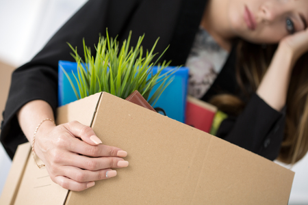 dismissal: Young dismissed female worker in office holding carton box with her belongings. Getting fired concept.