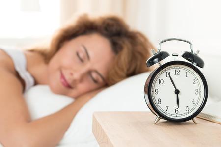 午前中に彼女の寝室で眠っている美しい幸せな女。幸福と健康的な睡眠の概念。