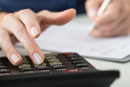office paper: Close up of female accountant or banker making calculations. Savings, finances and economy concept
