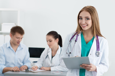 Portrait of beautiful smiling female medicine doctor holding file with documents with her colleague talking to male patient at background. Healthcare and medicine concept. Imagens