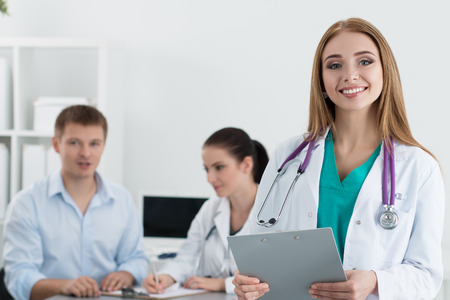 healthcare portrait: Portrait of smiling female medicine doctor with her colleague consulting male patient at background. Healthcare and medicine concept.
