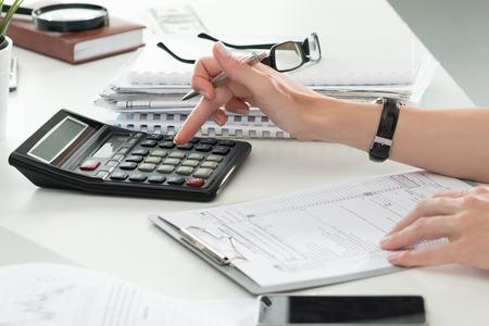 Close-up van vrouwelijke accountant of bankier maken van berekeningen. Besparingen, financiën en economie Het concept
