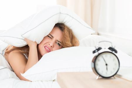reloj despertador: Mujer hermosa joven que odia levantarse temprano en la mañana. Muchacha soñolienta que mira el reloj de alarma y tratando de ocultar debajo de la almohada