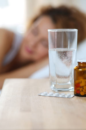 sleeping tablets: Glass of water and drugs standing on bedside table in front fo sleeping woman