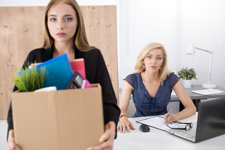 unemployed dismissed: Boss dismissing an employee. Dejected fired office worker carrying a box full of belongings. Getting fired concept.