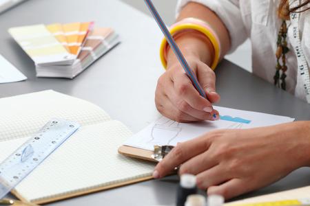 dressmaker: Close-up of adult female dressmaker drawing some clothing design Stock Photo