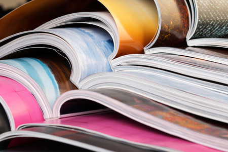printed: Close-up of stack of colorful magazines. Press, news and magazines concept