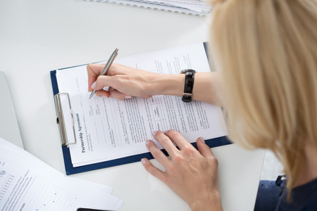 business partnership: Business woman filling partnership agreement blank. Business and partnership concept Stock Photo