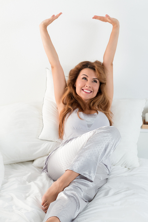 arms up: Young pretty woman stretches herself laying in her bed in the morning. Easy waking up and happy morning