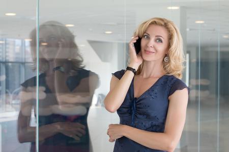ejecutivo en oficina: Retrato de la hermosa mujer adulta de negocios hablando por teléfono móvil de pie en su oficina Foto de archivo