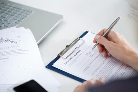 SECRETARIA: Mujer de negocios llenar acuerdo de asociaci�n en blanco. Negocios y concepto de asociaci�n. Documentos de firma Foto de archivo