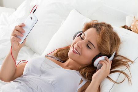 home audio: Young beautiful woman laying in her bedroom and listening to music of audio book. Leisure or study at home.