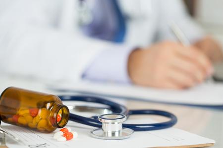 Pillen en stethoscoop leggen op knippen boord met recept leeg met mannelijke geneeskunde arts werken op de achtergrond. Werktafel geneeskunde arts. Gezondheidszorg en medische concept. Copyspace Stockfoto