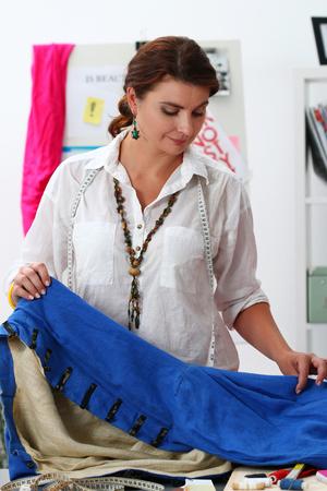 dressmaker: Fashion designer working in studio. Dressmaker woman