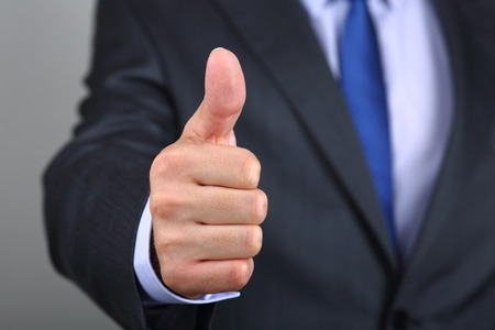business in hand: Close up of business man hand with thumb up. Approval positive gesture