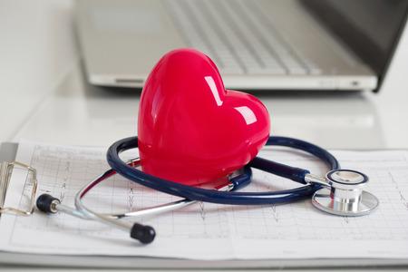 Lees hart en stethoscoop tot op cardiogram chart bij dokter werktafel close-up. Medische hulp, preventie, preventie van ziekte of verzekering concept.
