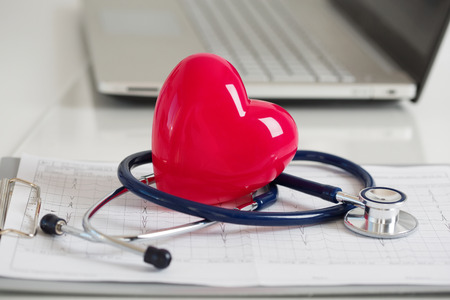 test: Read heart and stethoscope laying on cardiogram chart at doctors working table closeup. Medical help, prophylaxis, disease prevention or insurance concept. Stock Photo