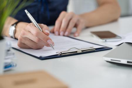 女性の手のクローズ アップ。女性は彼女のオフィスに座って何かを書きます。ドキュメントの署名 写真素材