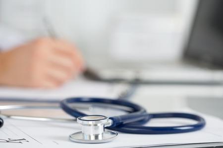 医学博士作業テーブル。聴診器に焦点を当てます。男性医学の医師は、バック グラウンドで動作しています。健康・医療コンセプト Copyspace 写真素材