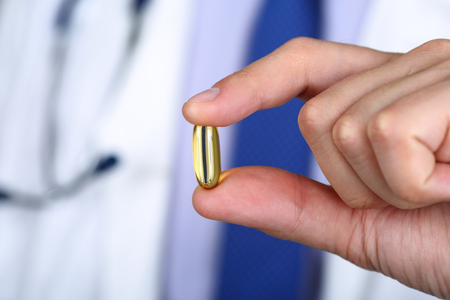 Primer plano de la mano masculina médico celebración de pescado cápsulas de gelatina blanda de aceite. Omega 3 ácidos. Concepto de alimentos saludables.