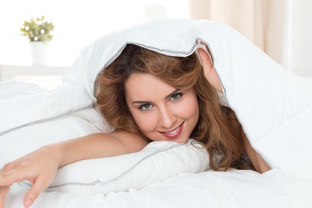 hair wrapped up: Young pretty woman hiding under the blanket. Girl in playful mood. Stock Photo