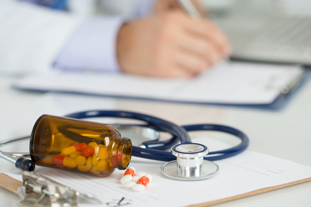 Pills and stethoscope laying on clipping board with prescription blank with male medicine doctor working on background. Medicine doctor's working table. Healthcare and medical concept. Copyspace