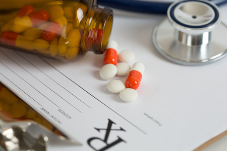 pharmacologist: Recipe form lying on a table with a stethoscope head and pills on it. Medicine or pharmacy concept.